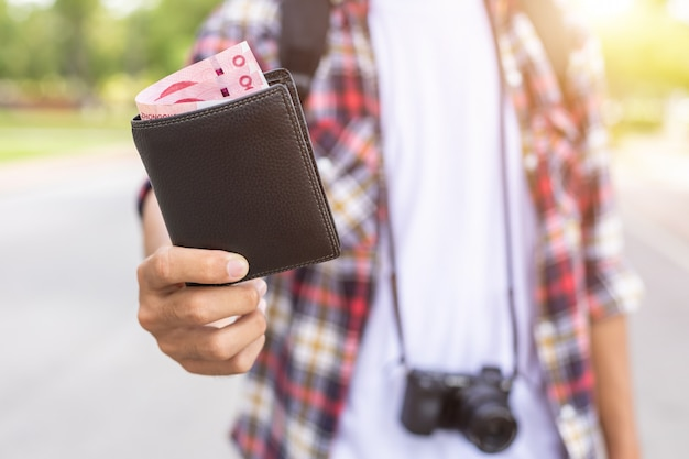 Mano del turista asiatico che dà banconota e portafoglio nero che ha trovato nell'attrazione turistica.