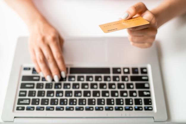 Mano dell'acquirente in linea femminile che tiene la carta di plastica sulla tastiera del computer portatile mentre inserisce il suo numero per pagare l'ordine