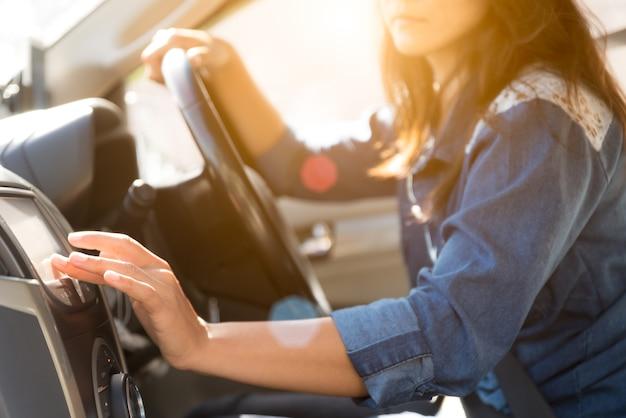 Mano dell'autista donna che tocca lo schermo nel sistema di navigazione.