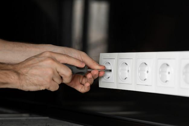 Mano dell'elettricista con un cacciavite che smonta una presa elettrica bianca su una parete di vetro nero.