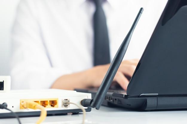 Mano dell'ingegnere di rete che scrive sulla tastiera del computer portatile accanto