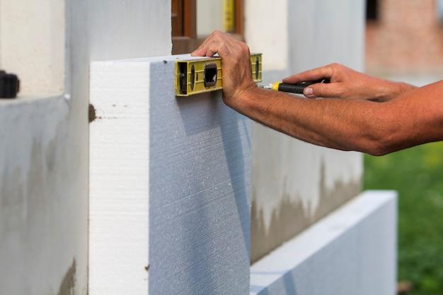 Mano dell'operaio con livello e coltello che misurano e tagliano il foglio di schiuma di poliuretano rigido bianco sul muro alla finestra di plastica appena installata. tecnologia moderna, ristrutturazione, concetto di isolamento.