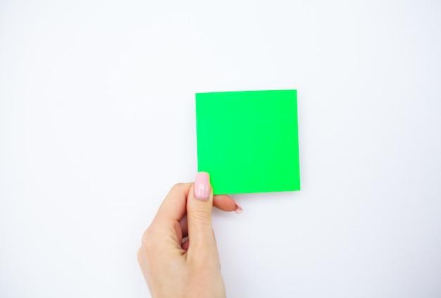 Mano dell'ufficio che tiene un autoadesivo di colore verde su fondo bianco