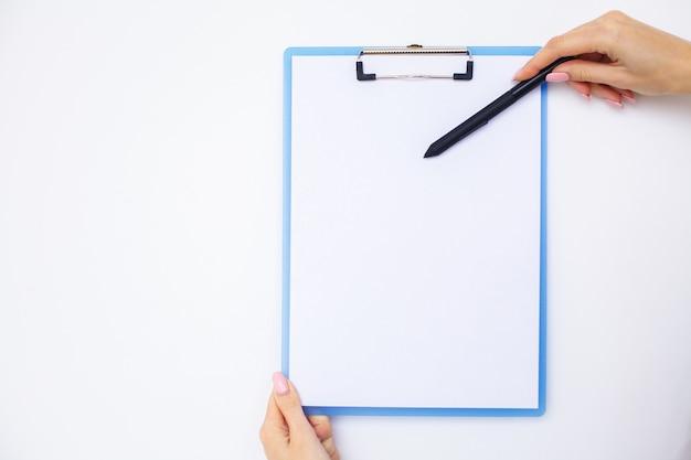 Mano dell'ufficio che tiene una cartella con una carta di colore bianco sullo sfondo della tabella bianca. copyspace.