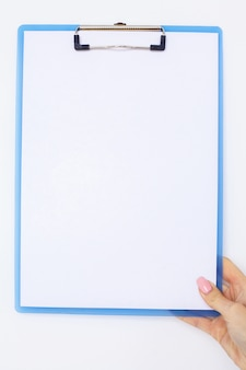 Mano dell'ufficio che tiene una cartella con una carta di colore bianco sullo sfondo della tabella bianca