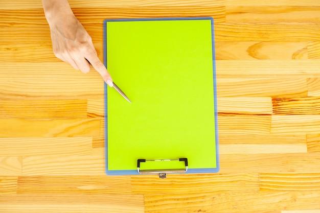 Mano dell'ufficio che tiene una cartella con una carta e una penna di colore verde