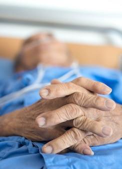 Mano dell'uomo anziano che dorme in un ospedale