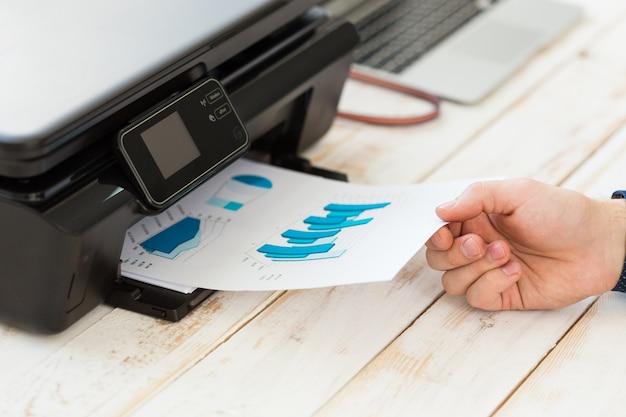Mano dell'uomo che fa le copie. lavorare con la stampante