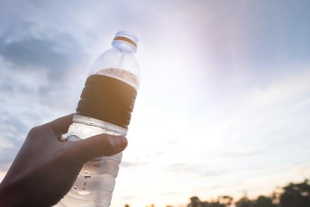 Mano dell'uomo che tiene una bottiglia di acqua sul cielo