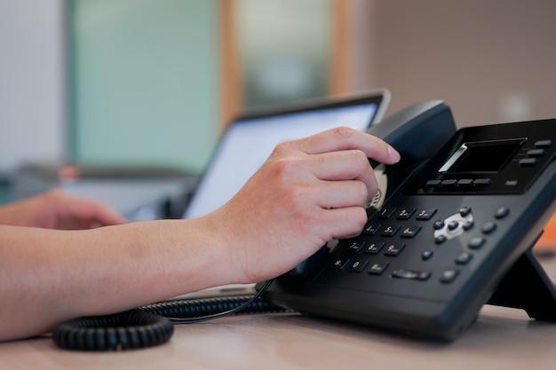 Mano dell'uomo che tocca il telefono del ricevitore per chiamare