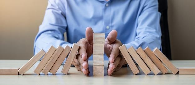 Mano dell'uomo d'affari che arresta i blocchi o domino di legno di caduta