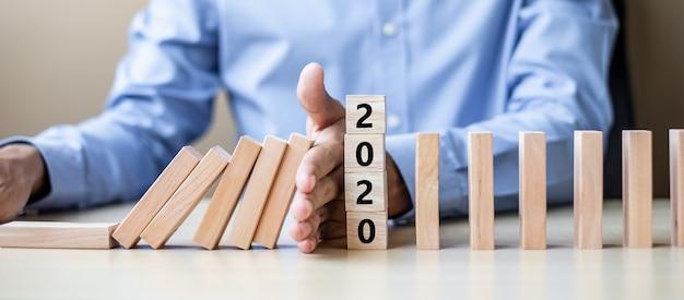 Mano dell'uomo d'affari che ferma l'effetto domino sopra il blocco 2020