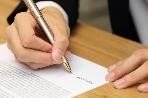 Mano dell'uomo d'affari che firma una carta del contratto