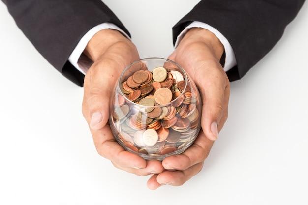 Mano dell'uomo d'affari che mette le monete sul vetro, concetto di risparmio di denaro per la contabilità delle finanze