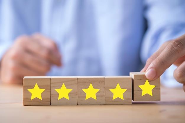 Mano dell'uomo d'affari che mette stella gialla che è stampata sul cubo di legno. sondaggio sulla valutazione del cliente e concetto di soddisfazione.