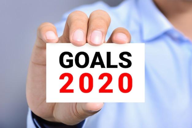 Mano dell'uomo d'affari che mostra carta con gli obiettivi 2020 del testo