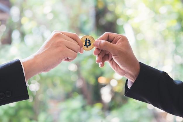 Mano dell'uomo d'affari che passa la moneta dorata del bitcoin di criptovaluta in ufficio.