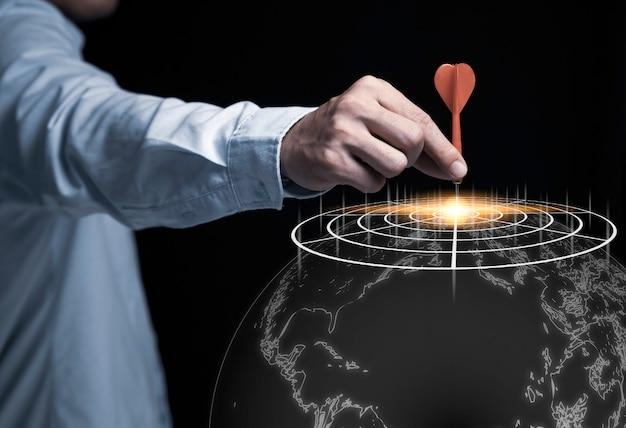 Mano dell'uomo d'affari che tiene e che lancia dardo rosso per mirare a bordo su fondo nero e mappa di mondo concetto dell'obiettivo di investimento e di affari.