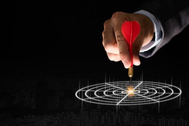 Mano dell'uomo d'affari che tiene e che lancia dardo rosso per mirare al bordo su fondo nero concetto dell'obiettivo di investimento e di affari.