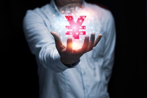 Mano dell'uomo d'affari che tiene il segno di yen o yen con luce solare e il nero