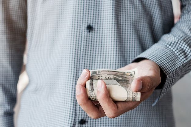 Mano dell'uomo d'affari che tiene la pila della banconota di yen giapponesi. concetti di affari, denaro, investimenti, finanza e pagamento