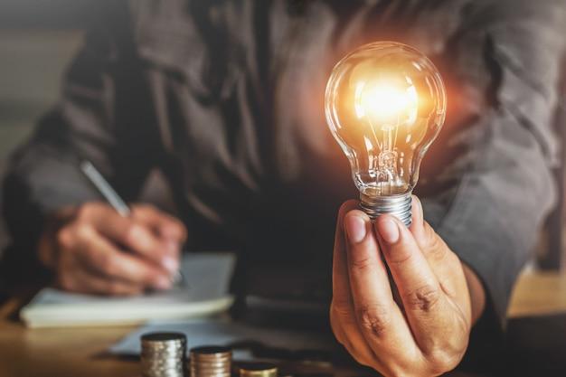 Mano dell'uomo d'affari che tiene lampadina. concetto di idea con innovazione e ispirazione