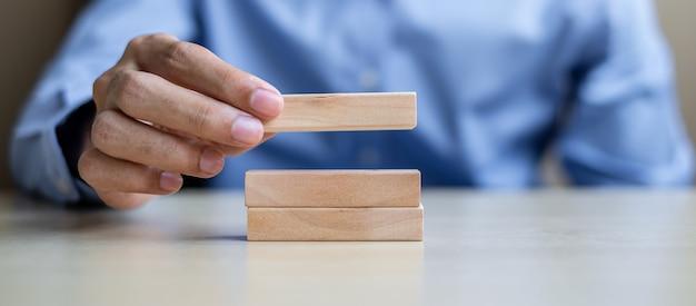 Mano dell'uomo d'affari che tiene le particelle elementari di legno sulla tavola