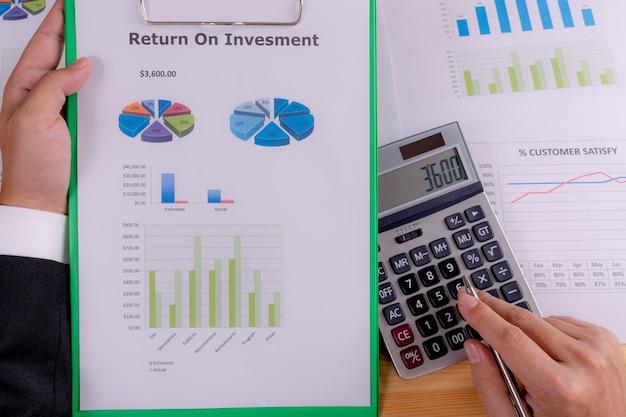 Mano dell'uomo d'affari che tiene rapporto finanziario di ritorno sull'investimento (roi).