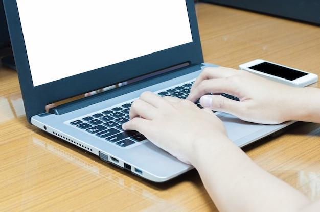 Mano dell'uomo d'affari facendo uso del computer portatile per lavorare duro sullo schermo bianco