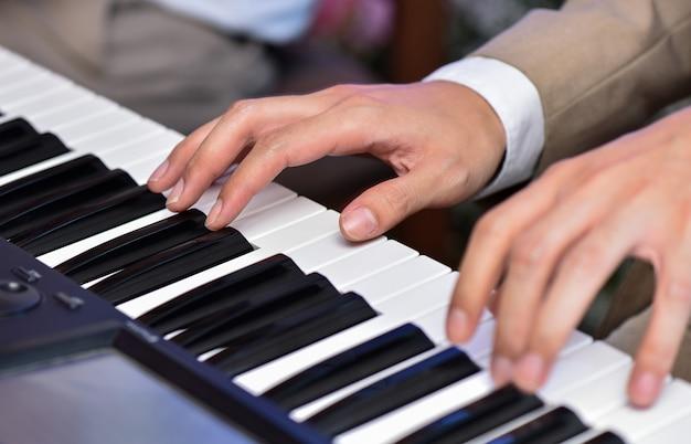 Mano dell'uomo del primo piano che gioca piano su nozze o sul concerto