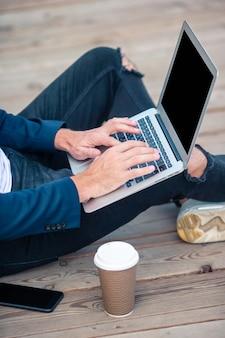 Mano dell'uomo del primo piano che lavora al ponte di legno con il computer portatile