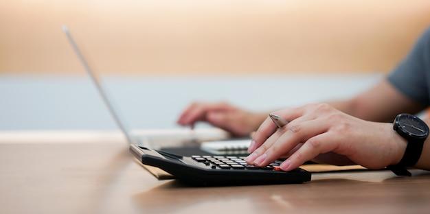 Mano dell'uomo dell'impiegato del ragioniere che preme sul calcolatore e sulla tastiera di battitura a macchina sul computer portatile