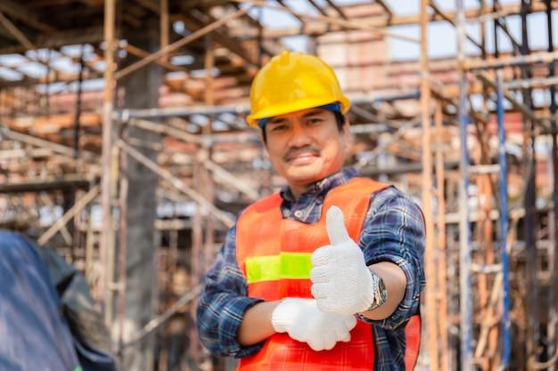 Mano dell'uomo dell'ingegnere / lavoratore che dà pollice su sopra il cantiere vago, riuscito concetto