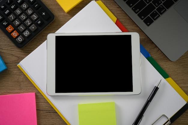 Mano dell'uomo di affari che lavora al computer portatile sullo scrittorio di legno