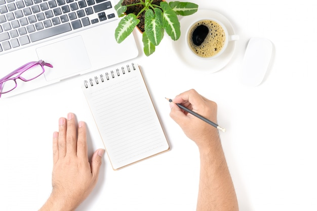 Mano dell'uomo di affari che scrive sul taccuino in bianco con il computer portatile e il caffè isolato su fondo bianco, vista superiore e spazio della copia