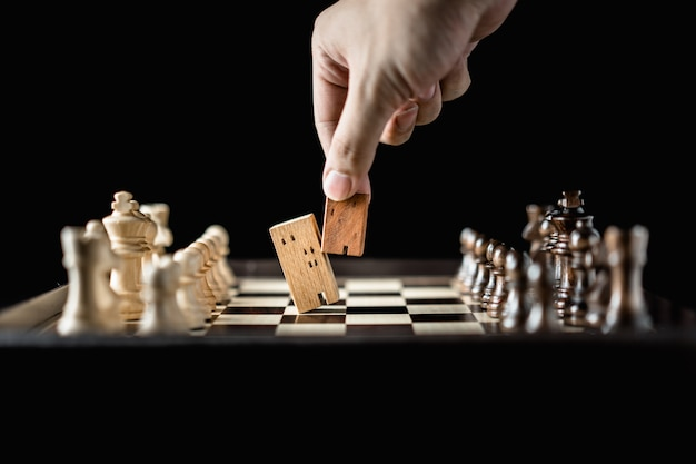 Mano dell'uomo di affari che sposta gli scacchi a costruire e ad alloggiare i modelli nel gioco di scacchi