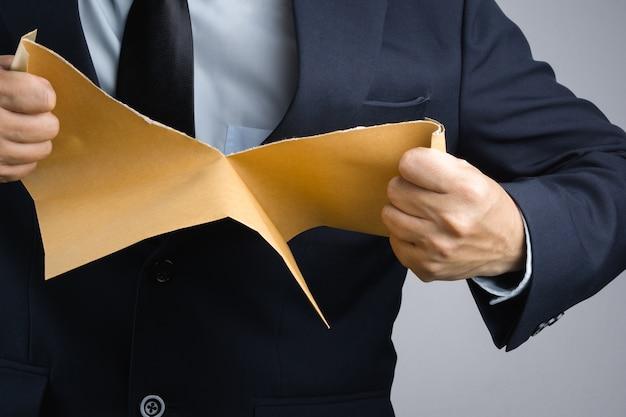 Mano dell'uomo di affari che strappa il documento marrone autorigolante della busta nella rabbia
