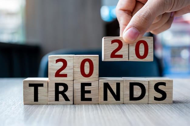 Mano dell'uomo di affari che tiene cubo di legno con le tendenze 2020