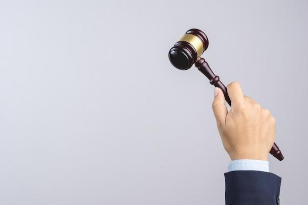 Mano dell'uomo di affari che tiene il martelletto del giudice in legno come una legge o segno di giustizia