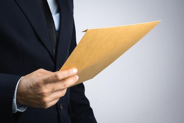 Mano dell'uomo di affari che tiene un documento marrone autoportante della busta