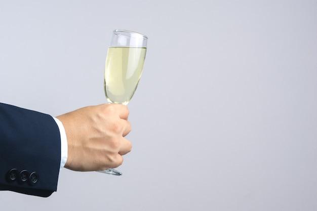 Mano dell'uomo di affari che tiene vetro di champagne per la celebrazione