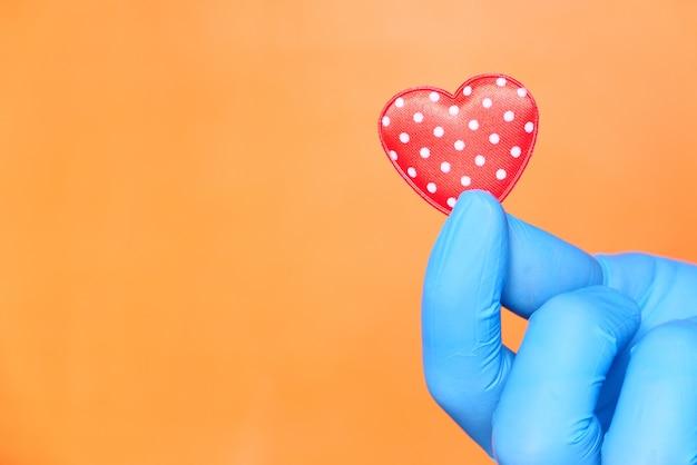Mano dell'uomo in guanti protettivi che tengono cuore rosso.