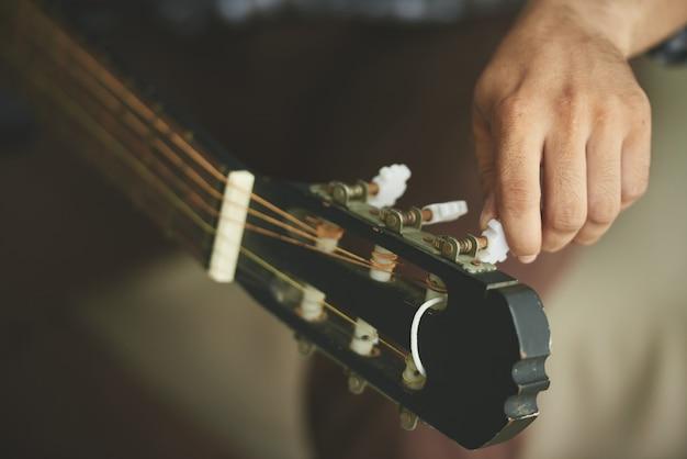 Mano dell'uomo irriconoscibile che gira le spine di accordatura della chitarra acustica