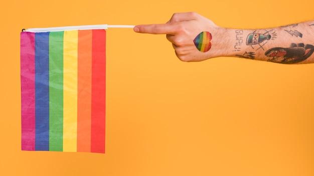 Mano dell'uomo omosessuale che tiene la bandiera lgbt