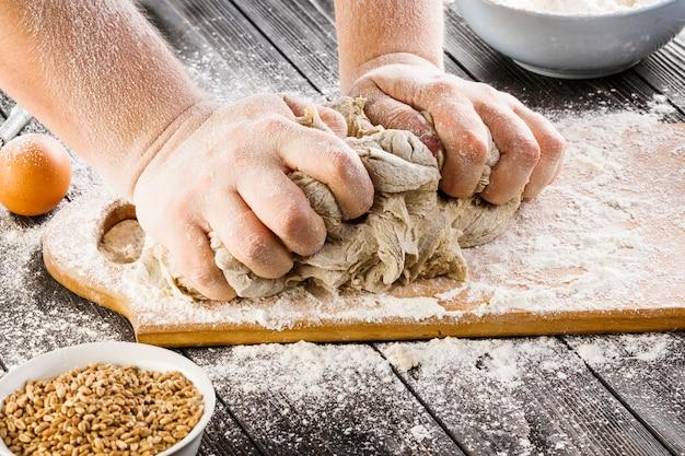 Mano dell'uomo preparando pasta e chicchi di grano nella ciotola sul tavolo