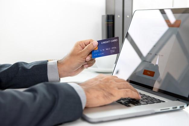 Mano della carta di credito della tenuta dell'uomo d'affari che effettua pagamento online con il computer portatile