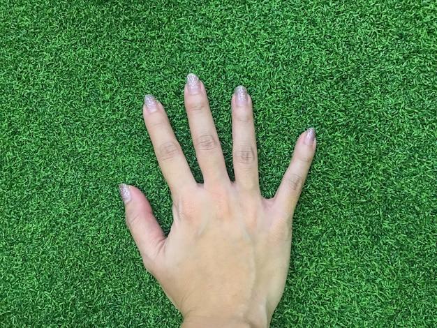 Mano della chiodo della mano della donna che tocca la superficie a pascolo verde.