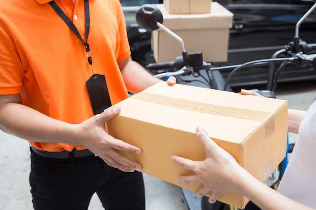 Mano della donna che accetta una consegna di scatole dal fattorino, consegna merci tramite servizio di moto, trasporto veloce e gratuito