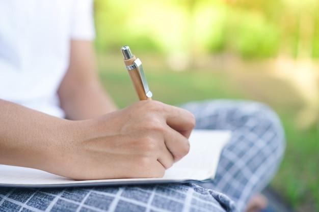 Mano della donna che annota in piccolo taccuino bianco per prendere una nota da non dimenticare o per fare il piano della lista.
