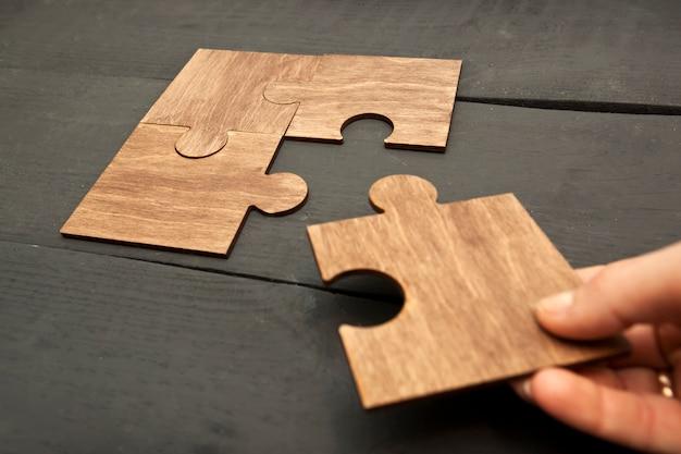 Mano della donna che collega i puzzle l'un l'altro